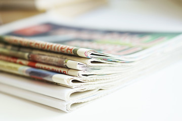 Newspapers folded and stacked in a pile. Stack of daily journals with news, partially shown headlines and articles. Side view, selective focus