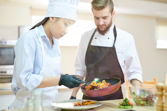 Portrait of female Asian chef cooking delicious dishes while working in modern restaurant kitchen with su-chef, copy space