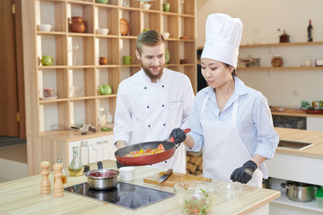 Portrait of Asian female chef cooking vegetables holding frying pan over stove in modern restaurant kitchen, copy space