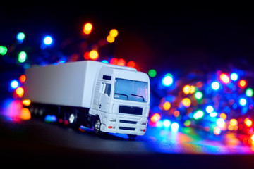 White miniature plastic toy truck against a black background with blurred christmas lights in blue, red, yellow, orange and green