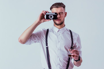 Handsome and stylish man in white shirt and suspenders making photo on old vintage camera and holding glass of whiskey in hand while standing against gray background. Elegant man took photo in studio