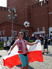 A supporter of the Polish national soccer team plays with a ball in front of the Kremlin's Spasskaya Tower at Red Square in Moscow