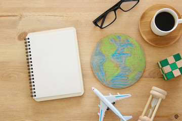 top view image of airplane , earth globe and coffee over wooden background.