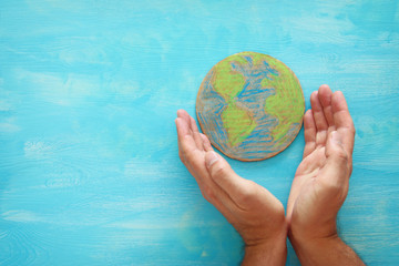 top view image of man hands holding earth globe over blue wooden background.