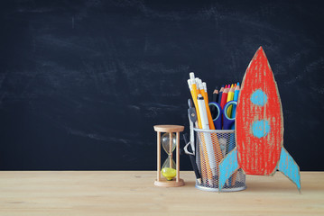 Back to school concept. rocket and pencils in front of classroom blackboard.