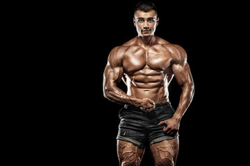 Muscular young fitness sports man. Workout with dumbbell in fitness gym. Copy space for fitness nutrition ads.
