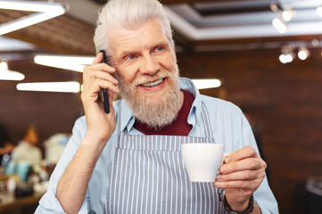 Coffee break. Joyful mature male person holding cup in left hand and looking aside, waiting for client