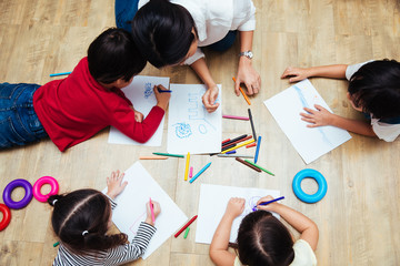 Top view Family happy children group kid boy and girl kindergarten paint drawing on peper with teacher education together