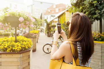 Woman on city tour taking picture of beautiful cafe flowers with her smartphone