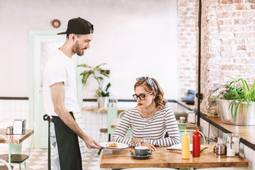 Waiter in black cap giving burger to pretty lady in eyeglasses which sitting at the table in cafe