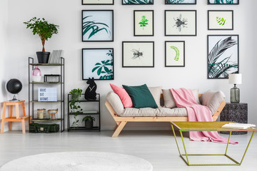 Gold metal table standing in white living room interior with decor on black metal racks, fresh green plants, light grey sofa with cushions and pink blanket and posters hanging on the wall