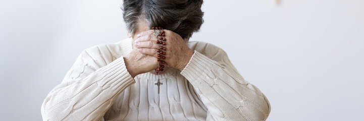 Panorama of catholic grandmother praying with rosary in the church