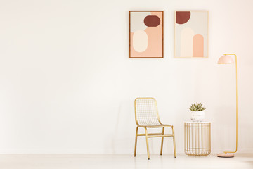 Real photo of a gold chair standing next to a small table with a plant and a yellow lamp in a minimal living room interior with two posters on a wall