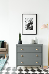 Black and white poster hanging on the wall above grey cupboard with decor standing in white room interior with checkerboard linoleum floor