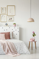 Pink, old-fashioned phone on a wooden side table and a pendant lamp in a serene bedroom interior with white walls
