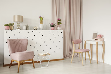 Elegant armchair and an open book by a polka dot wall, wooden vanity and curtains in a white bedroom interior with dirty pink elements