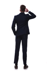 rear view of businessman scratching his head and thinking