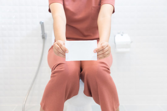 Woman holding sanitary napkins and sitting on toilet - woman on her period