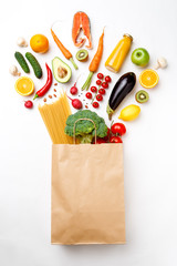 Photo of paper bag with vegetables, fruits, fish and spaghetti