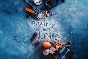 Header with baking tools and ingredients on a stone kitchen table. Baking with Love text made with flour. Food typography concept with copy space.
