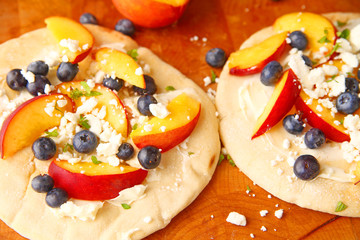 Small fruit pizzas with mascarpone, fresh blueberries and peaches with crumbled feta cheese on top