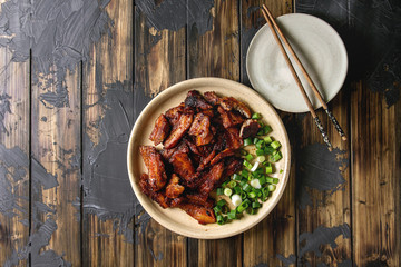 Chinese traditional dish Cantonese BBQ Pork Belly with spring onion served in ceramic plate with chopsticks over dark wooden plank background. Flat lay, space. Asian style dinner.