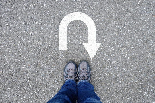 Outdoor shoes standing at u turn sign