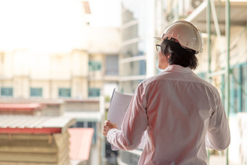 Engineer or Architect checking architectural drawing while wearing a personal protective equipment safety helmet at construction site. Engineering, Architecture and construction business concepts