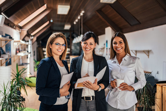 Three female colleagues at a work meeting smiling to camera.