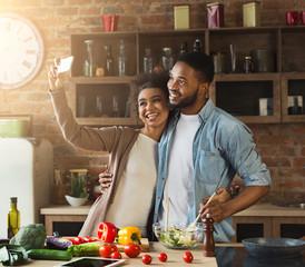 Happy black couple taking selfie at kitchen