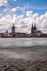 Köln Panorama mit dem Kölner Dom der Groß St. Martinskirche und der Hohenzollernbrücke, bewölkter Himmel und Wellen im Rhein