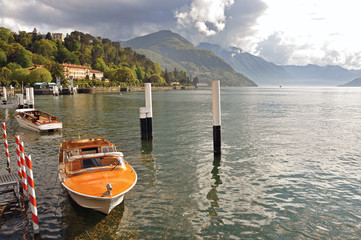 View of Lake Como in a cloudy day with motorboat and harbor in Bellagio, a charming village between the lake and the mountains of Alps. Lombardy region, northern Italy