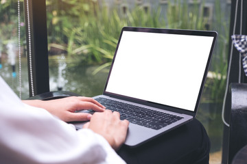 Mockup image of woman's hands using and typing on laptop with blank white desktop screen while sitting in cafe