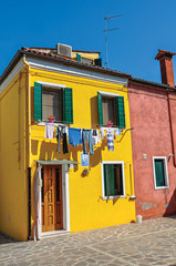 View of colorful terraced houses and clothes hanging in an alley on sunny day in Burano, a gracious little town full of canals, near Venice. Veneto region, northern Italy