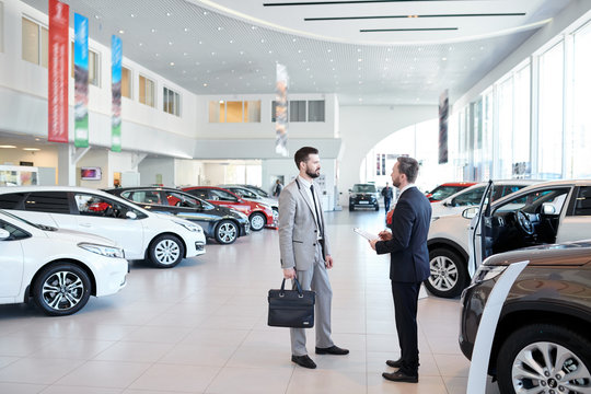 Full length portrait of handsome car salesman talking to customer in luxury showroom, copy space