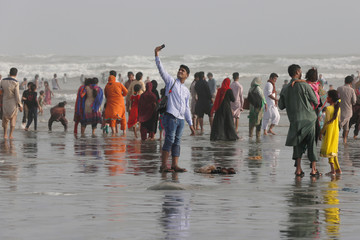 A man takes a selfie while visiting Clifton beach during Eid al-Fitr celebrations, in Karachi,