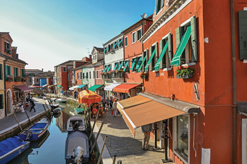 View of colorful buildings, people and boats in front of a canal at Burano, a gracious little town full of canals, near Venice. In the Veneto region, northern Italy