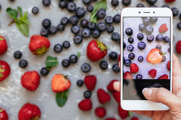 Photographing food. Hands taking picture of organic fresh harvested berries with smartphone