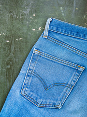 Blue jeans pocket on old wooden background. Top view