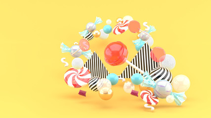 Candy among colorful balls on orange background.-3d rendering..
