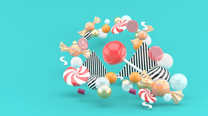 Candy among colorful balls on blue background.-3d rendering..