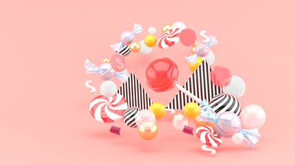 Candy among colorful balls on pink background.-3d rendering..