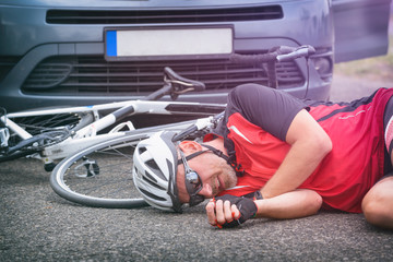 Cyclist lying on the road after hitting by a car