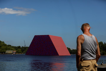Pedestrians walk past 'The London Mastaba' by artist Christo as it sits on the Serpentine in Hyde Park, London