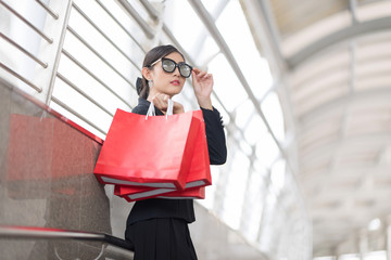 Attractive and Exusive Business Woman Wearing Modern Sunglasses With Lot of Red Shopping Bags. Happy After Working Hard.