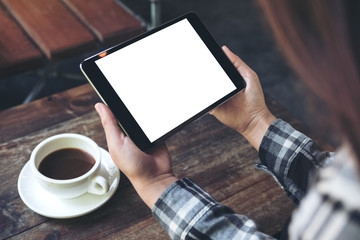 Mockup image of a woman holding black tablet pc with white blank screen with coffee cup on table background
