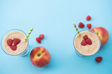 Peach smoothies with milk (yogurt), raspberries and striped straws. Blue background. Copy space top view