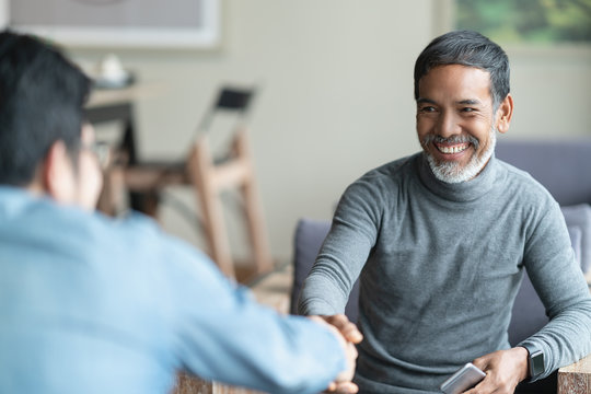 Confident mature Asian man sitting, smiling and shaking hand with partnership after making profitable agreement. Smart man handshake, deal and greeting concept.