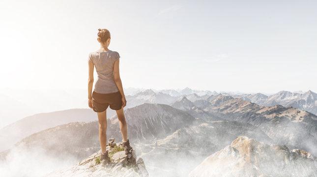 Frau steht auf einem Berggipfel am Morgen