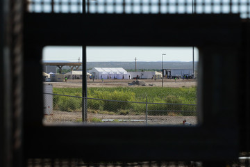 Children of detained migrants play soccer at a newly constructed tent encampment as seen through a border fence near the U.S. Customs and Border Protection port of entry in Tornillo